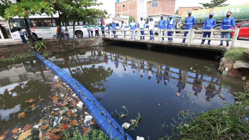 A barreira é construída de forma simples, com uma rede que envolve uma série de bombonas plásticas que flutuam, podendo acompanhar as mudanças do nível de água do canal, além de contar com estacas presas às margens para fixá-la.